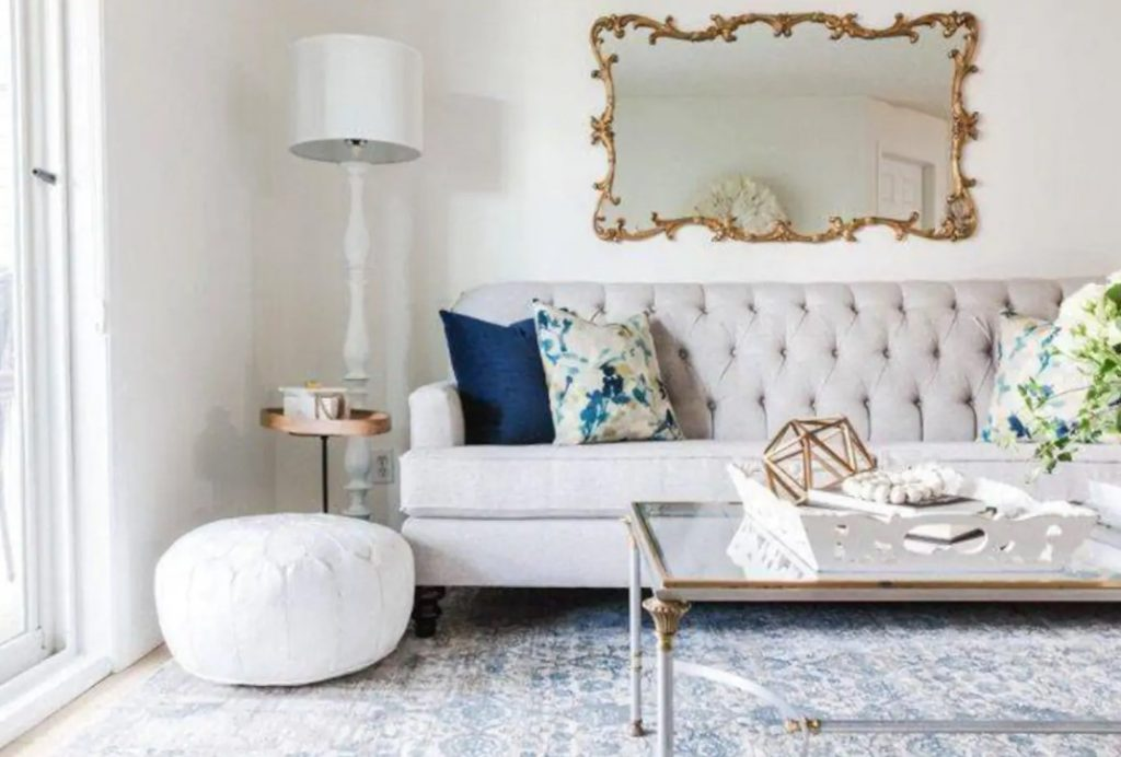 A luxuriously decorated living room with a gold gilt mirror, a lage sofa, and a glass coffee tabl