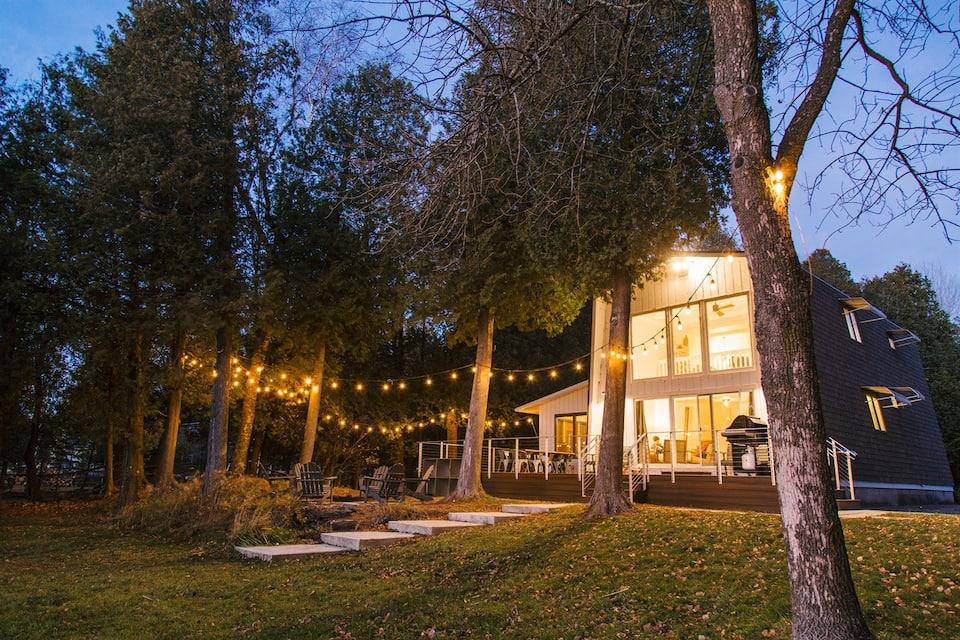 Twilight photo of a Door County cabin with floor to ceiling windows, large deck and outdoor white lights illuminating the back yard.