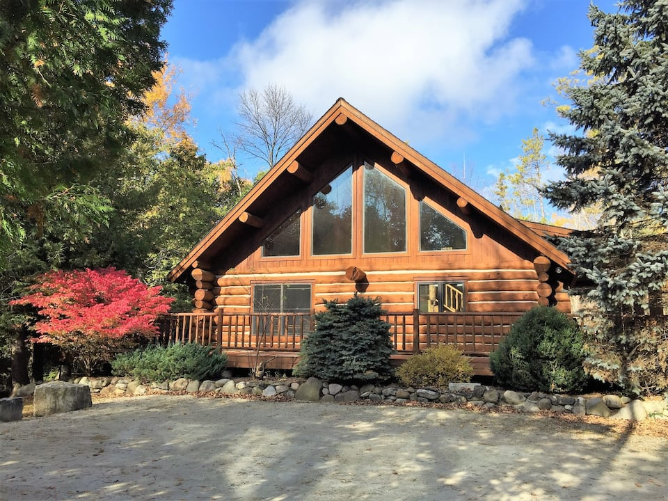 Beautiful Wisconsin log cabin rental with large windows and surrounded by beautiful landscaping.