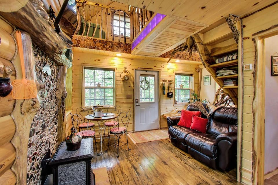 Cozy chic living space of one of the best cabins in Wisconsin with knotty pine walls and plank wooden floors.