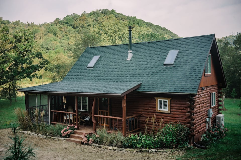 Rustic log cabin with cozy front porch and green roof.