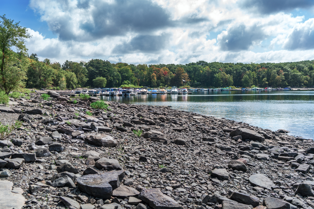 Rocky beach shore of Lake Wallenpaupack in small town Pennsylvania. Blue lake waters and marina in background.