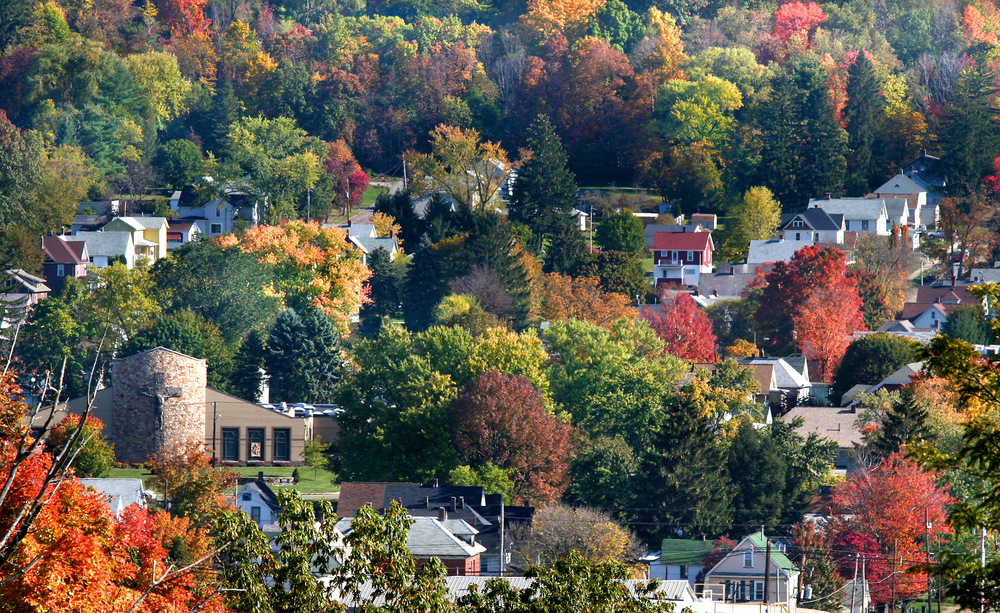 Small Pennsylvania town nestled into hillside with bright autumn colored leaves