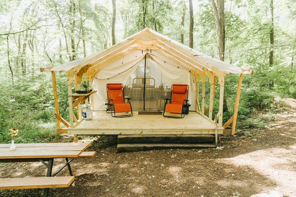 A large white tent in the woods with a private deck, outdoor chairs, and a picnic table outside of it.