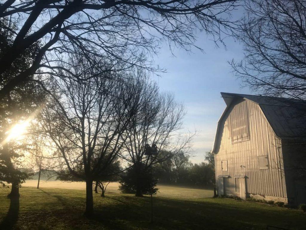 A modern barn turned farmhouse at sunset in Nebraska