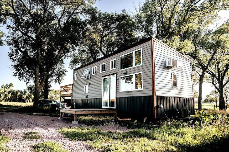 a gray and black tiny home in Nebraska surrounded by grass and trees