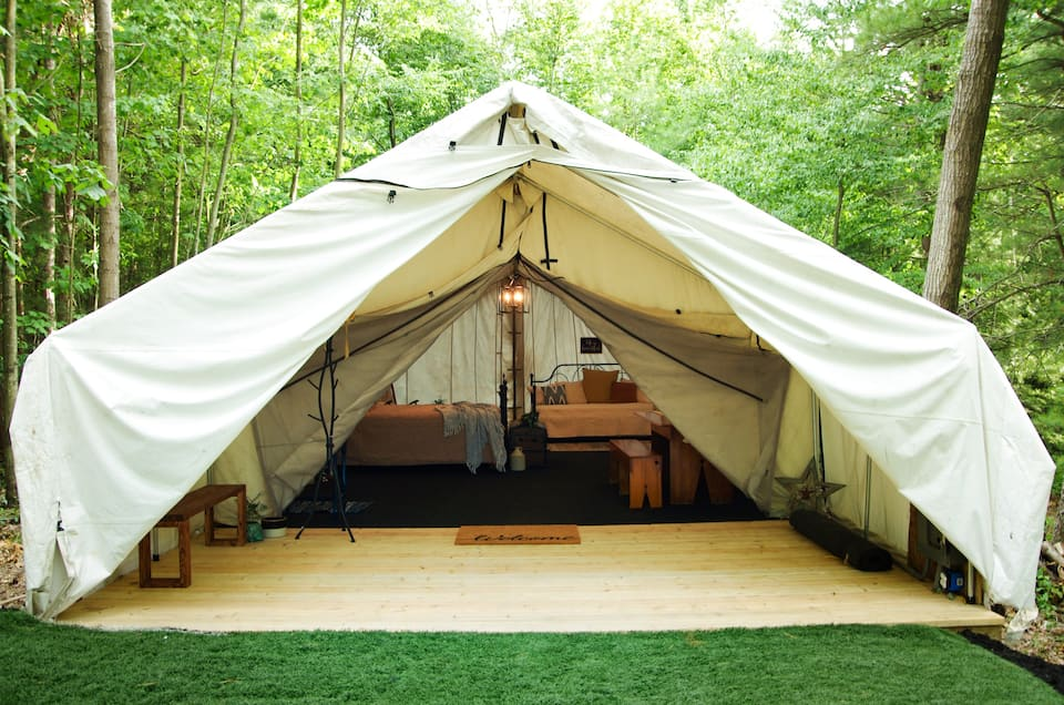 A large tent that has an entry space and then a large living space nestled against the woods