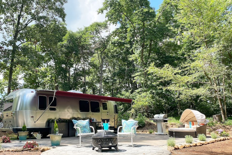 A vintage silver bullet airstream camper with a large patio that has seating, a fire pit, and a grill, nestled in the woods of Pennsylvania glamping in Pennsylvania