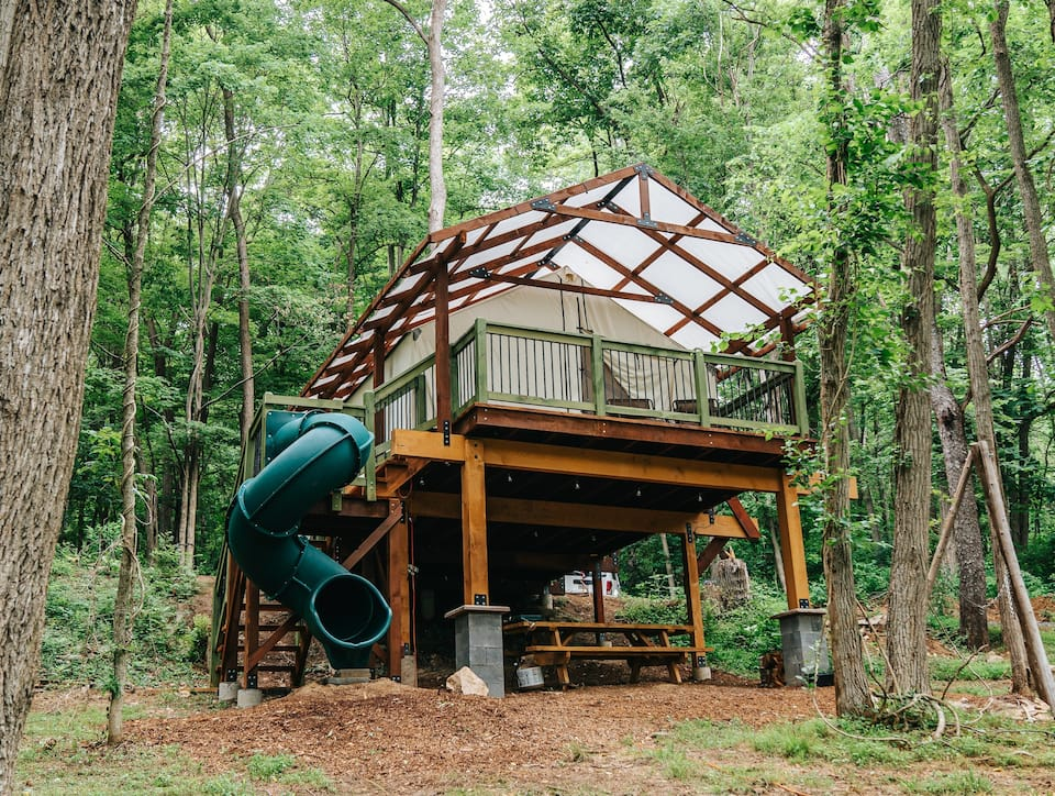 A large platform perched in the trees with a large white tent on it and a slide on the side as a way to get down to the ground