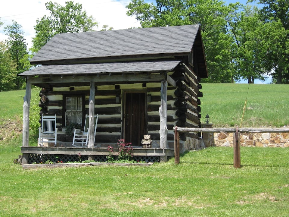 A traditional 1800s log cabin on the side of a grassy hill in Pennsylvania