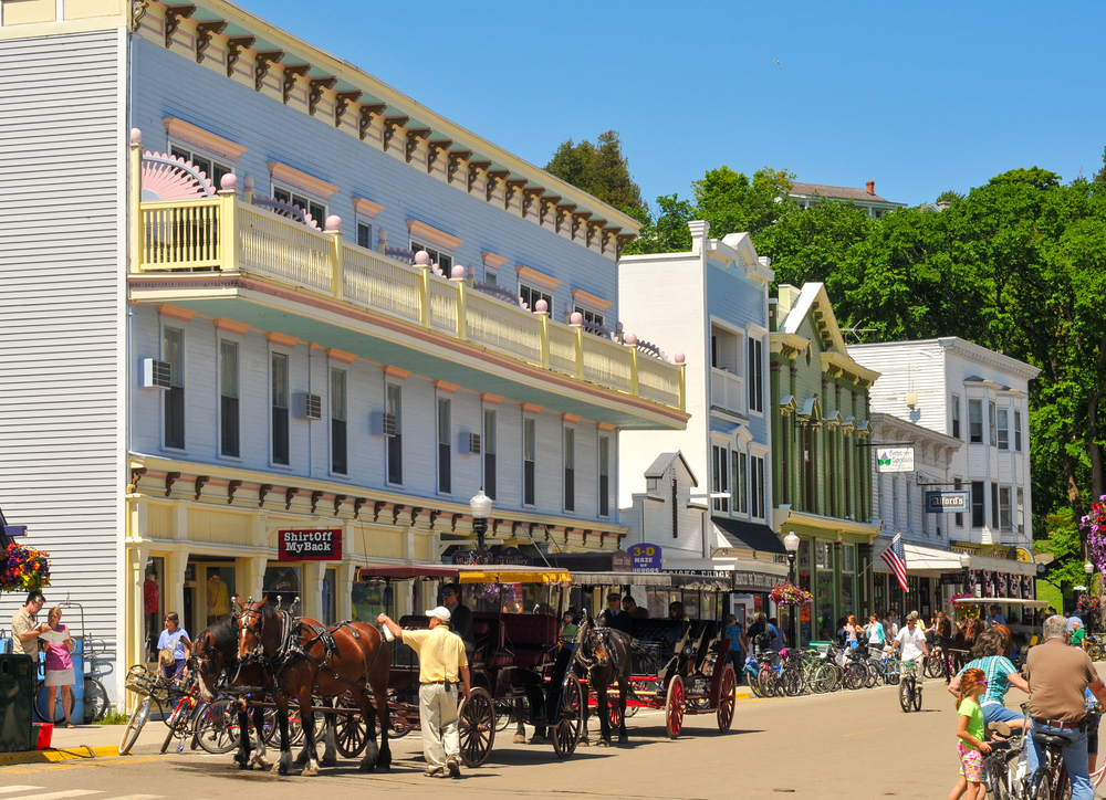 A street and horse drawn carriages on Mackinac Island one the small towns in Michigan great for a break