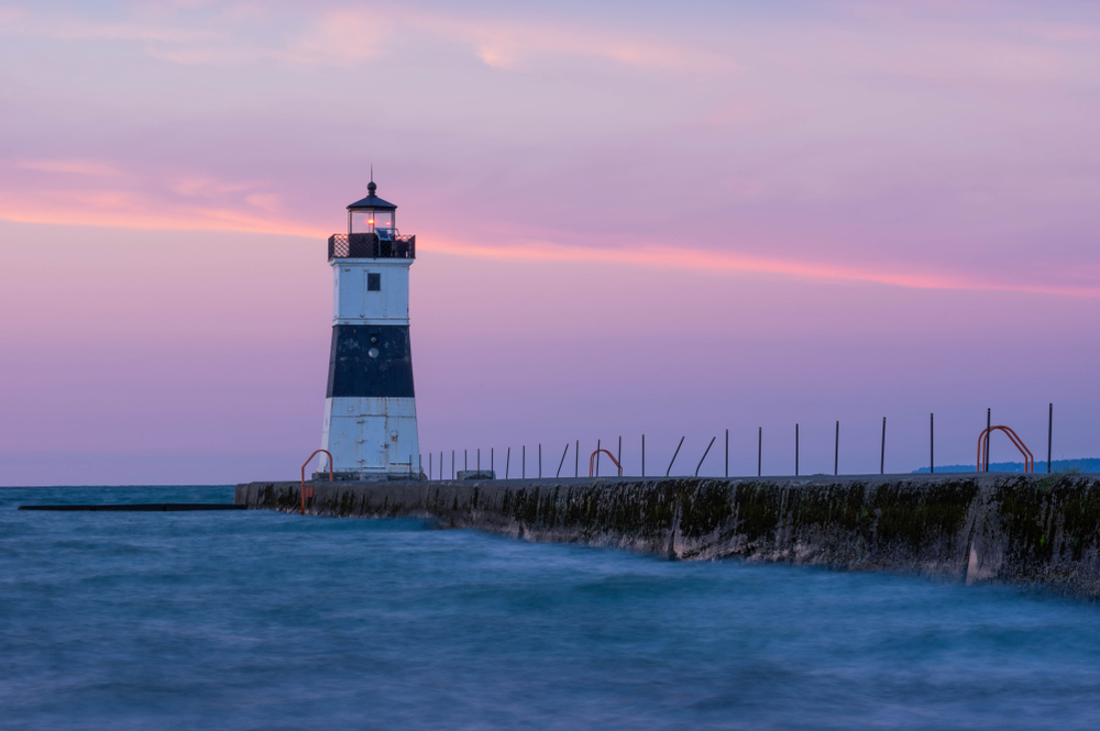 Lighthouse on Great Lakes in Erie as small town in PA. Pink sunset illuminates sky in background.