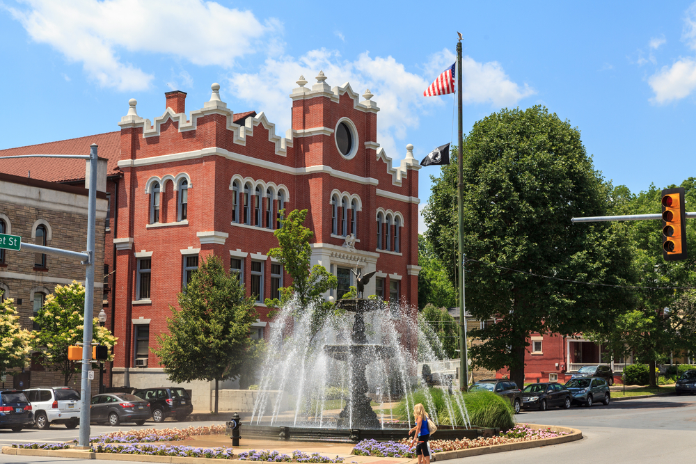 Bloomsburg a town in Pennsylvania with a beautiful fountain and vintage red-brick building in the distance.