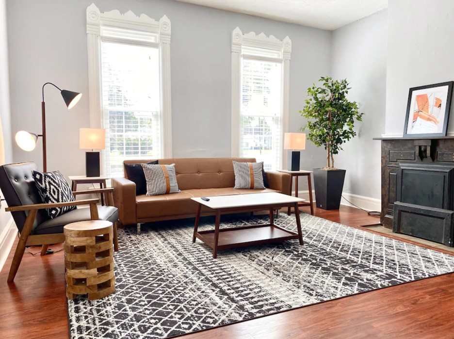 The living room of a historic home with a leather couch and side chair that was featured on HGTV VRBO in Ohio
