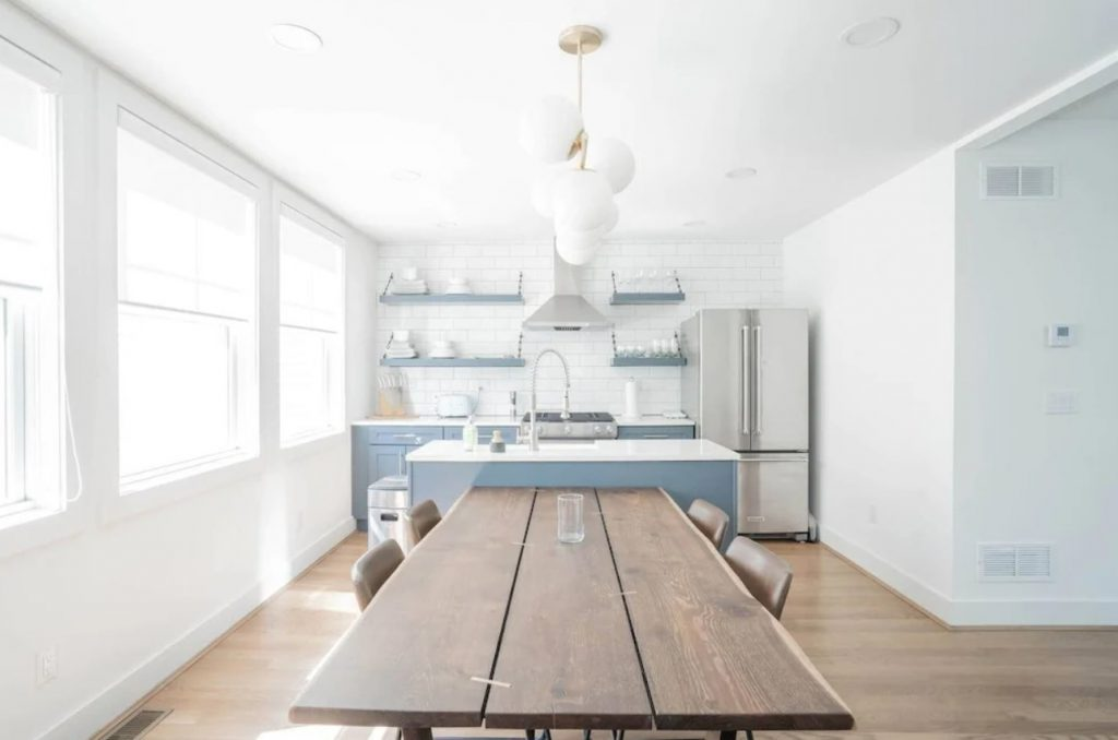 A modern kitchen with white subway tile, cornflower blue accents, and a wooden table.