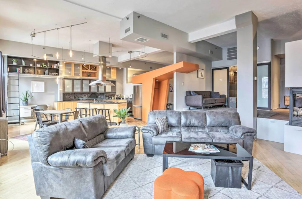The living space of a unique condo near Cleveland's stadiums, decorated in greys and oranges