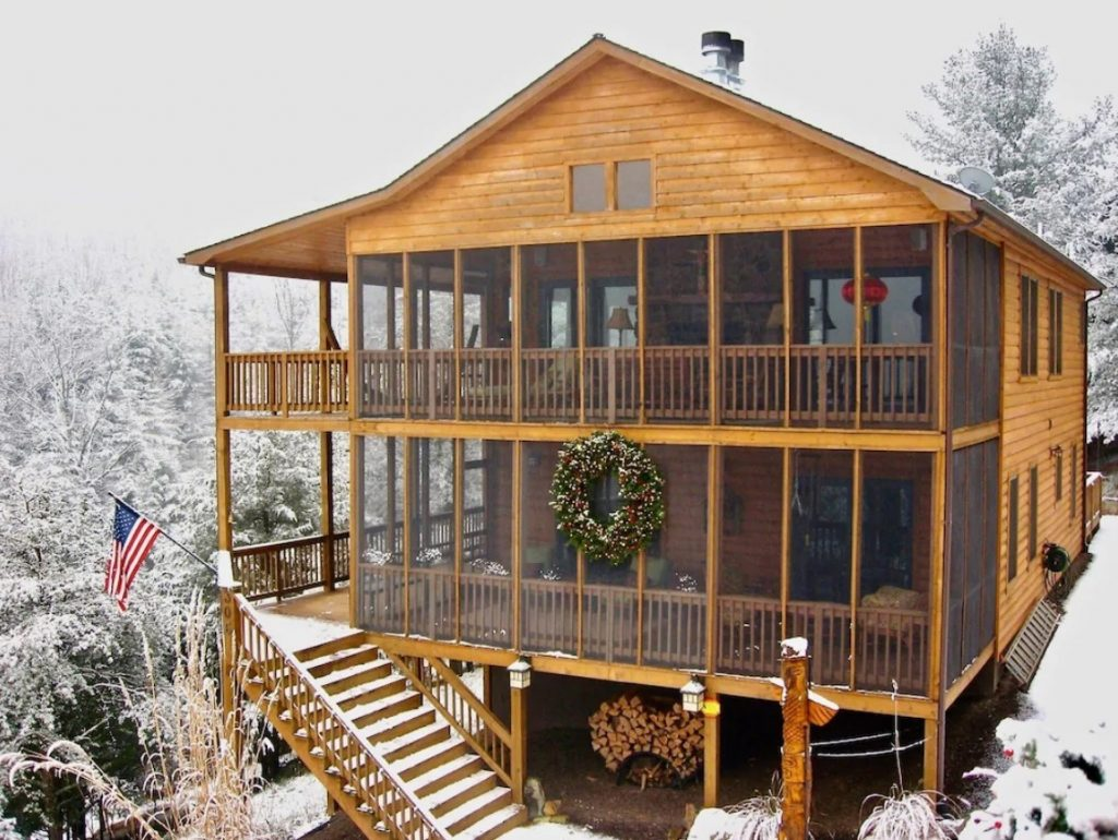 A very large cabin in the wintertime surrounded by the woods covered in snow. There are two massive screened in porches on the front of the house as well as a very large festive wreath. The cabin has an orange tint to it and plenty of windows and outdoor space.