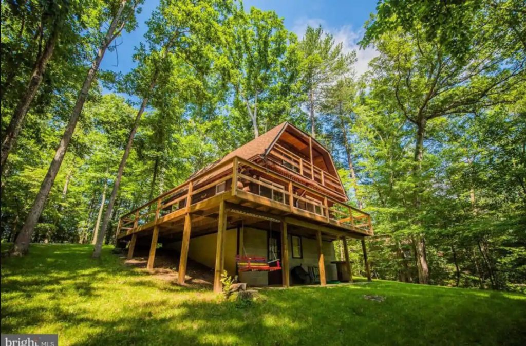 An orange colored cabin with a large wrap around deck, and a small patio beneath the deck with a porch swing. The top of the cabin is kind of squared off. The yard is very green and the cabin is surrounded by trees VRBO in West Virginia