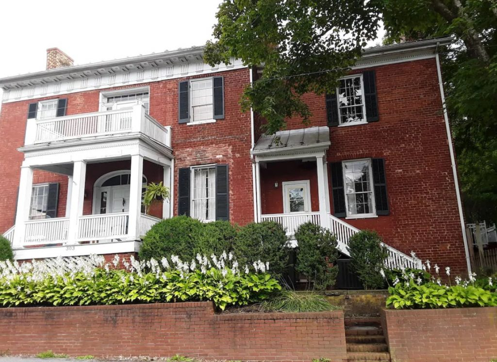 The exterior of a historic brick home that has white windows and doors with black shutters. In front of the large door is a small porch that is painted white. There are brick planters out front with green and white flowers and shrubs. VRBO in West Virginia