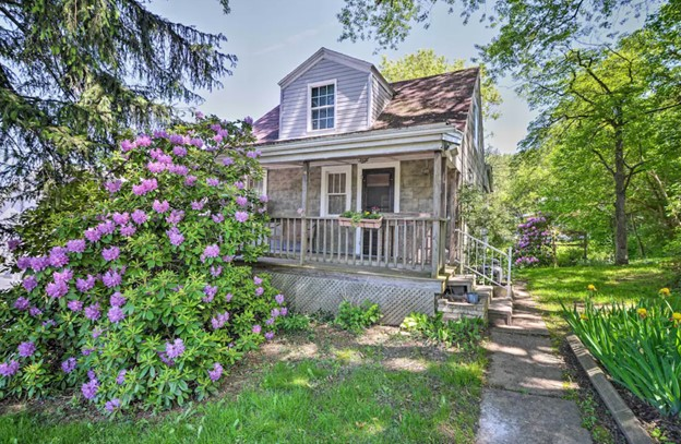 The exterior of a cute family home. It has stone on the front with a black door and white windows and a small porch. In front of it there are large bushes of purple flowers and yellow flowers. Its one of the best West Virginia VRBOs.