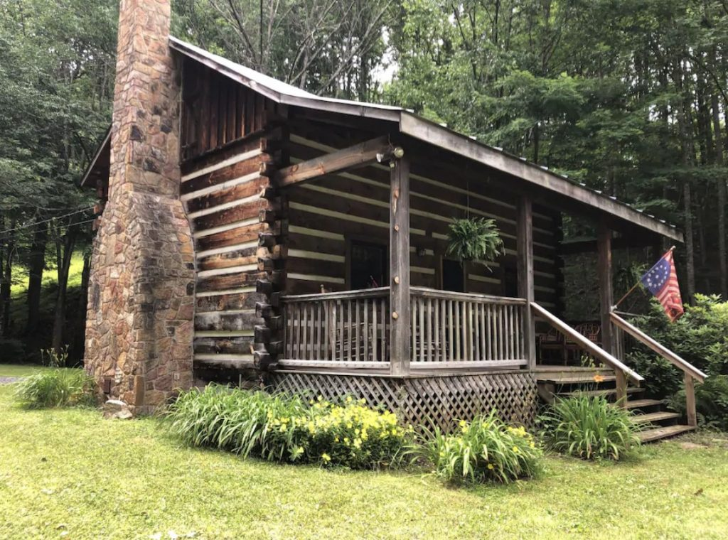 The exterior of a classic log cabin. There is a small covered front porch, a chimney outside, and an old American flag. The cabin is surrounded by plants with yellow flowers, a grassy area, and tall trees. Its a great West Virginia VRBO