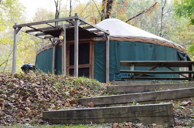 The exterior of a dark teal blue yurt with a white roof. There is a wooden lattice that covers the outdoor entryway and the wooden front door. There is a picnic table next to it, wooden steps going up the hill to the yurt, and dead leaves on the ground.