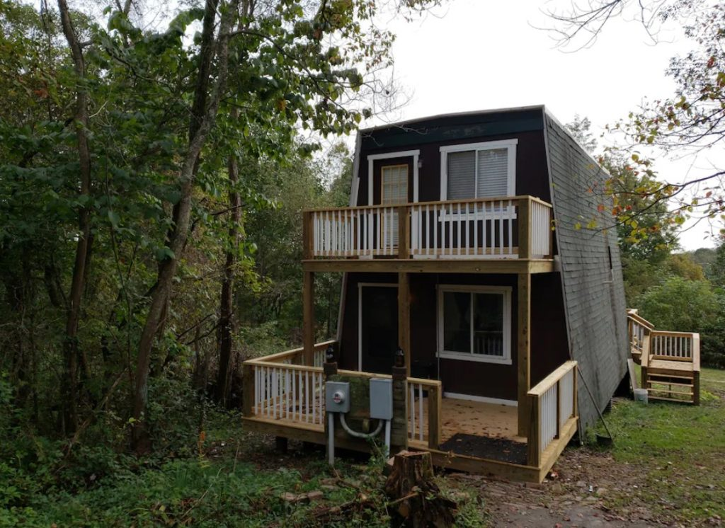 The exterior of the back of an A-frame cabin. It is painted black with white window trim. There are two decks, one on the bottom floor and one on the top floor. The cabin is surrounded by trees.