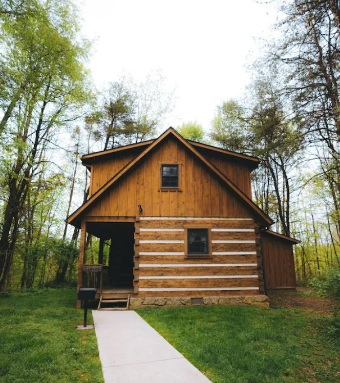 A natural wood cabin surrounded by trees and grassy lawn. It has sidewalk leading to a front porch, an a-frame shape, and a permanent grill right next to the sidewalk and front porch. It is one of the cutest cabins in Hocking Hills.