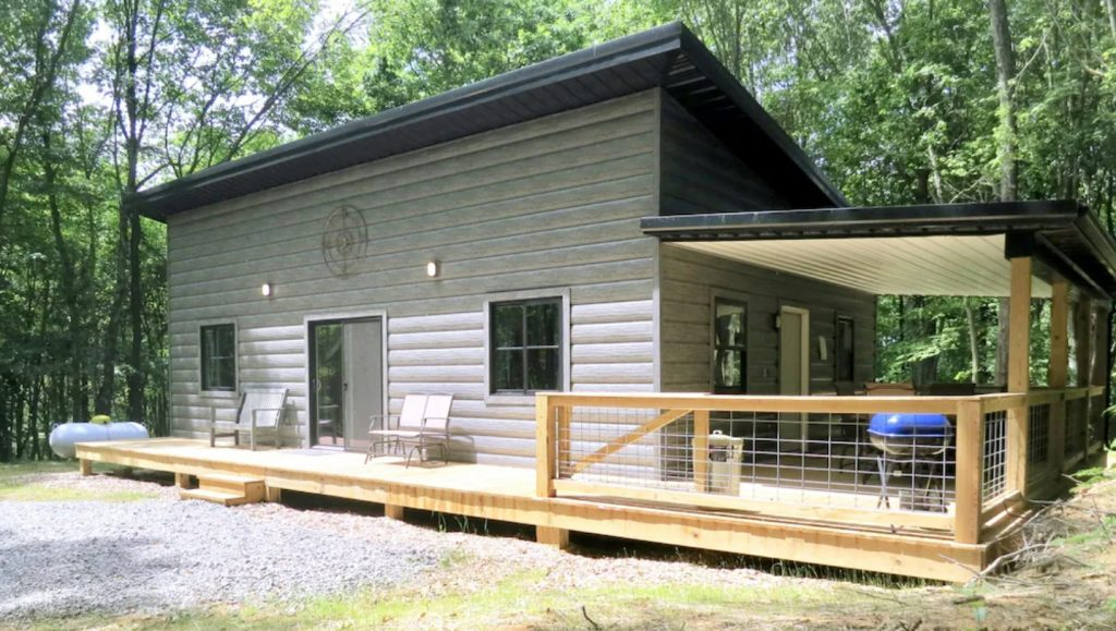 A large rectangular modern looking gray cabin. It has a porch of the side of it with a blue grill and the porch wraps around the front of the cabin as well. The cabin has a black roof and is surrounded by woods. It is one of the best cabins in Hocking Hills.