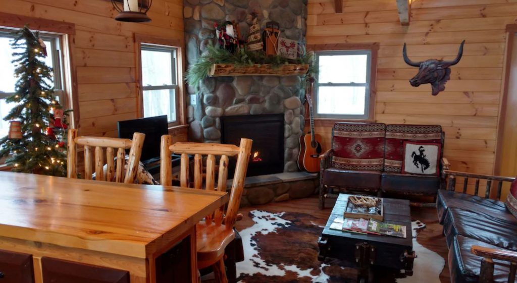 The interior of a classic log cabin. There is a large stone fireplace, two leather sofas with southwestern style pillows, a painting of a longhorn bull on the wall, and a Christmas tree behind a dining room table. There are Christmas decorations on the mantle of the stone fireplace and a guitar on the hearth.