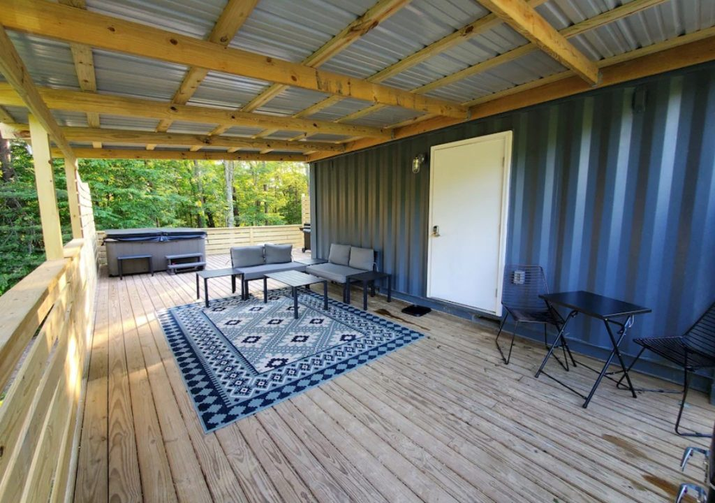 A large covered front porch on the side of a gray shipping container. There is black and grey patio seating, a rug that has a geometric design in shades of blue, and a hot tub. Behind the deck you can see trees.