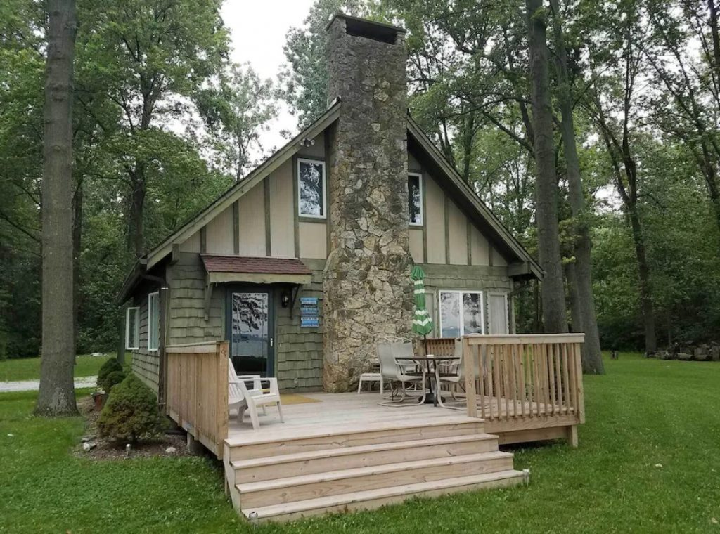 The exterior of a lakeside cabin. It has a large front porch, a stone chimney, and wood shingling on the side of the house. It is surrounded by a grassy lawn and trees.