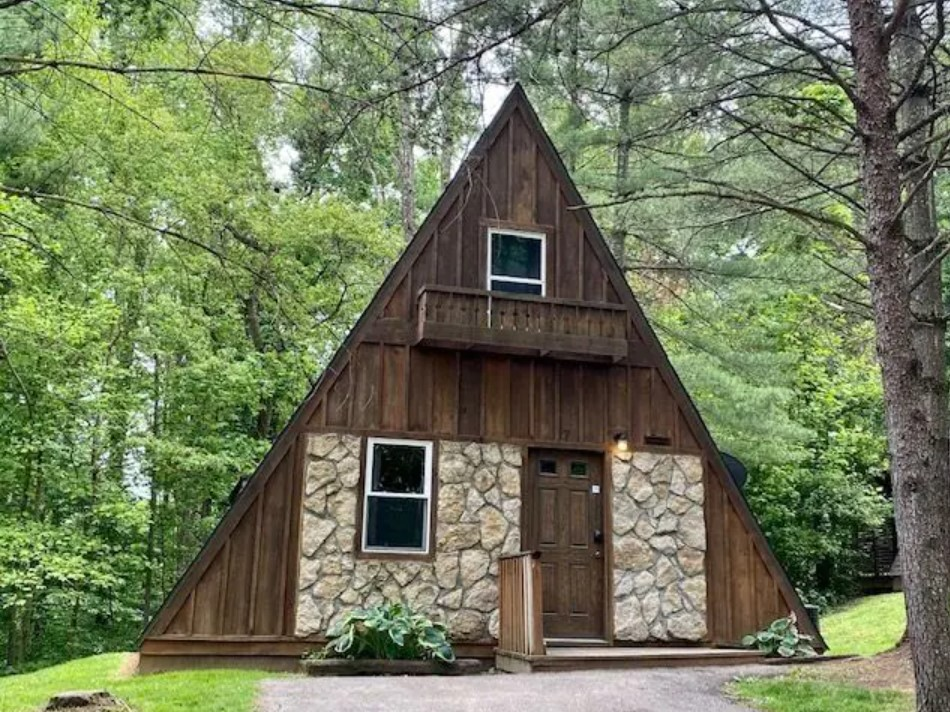 A classic A-frame cabin with dark wood paneling. There is stone one the front of the cabin next to the front door and front window. It is surrounded by trees with green leaves and a green lawn.