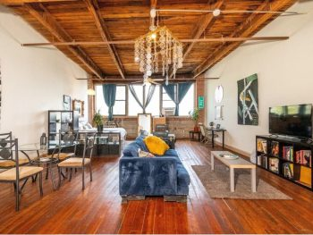 a loft in detroit with wood floors, wood ceilings, a blue velvet couch, and plenty of windows. It is one of the best Michigan Airbnb style options.