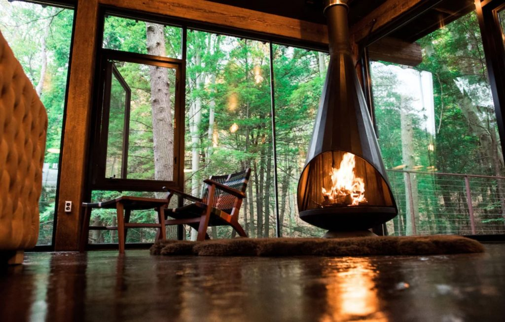 Looking up at a mod fireplace with a rug and woven chair in front of it. Behind it are glass walls and a glass window that is open. From the windows you can see a dense forest.