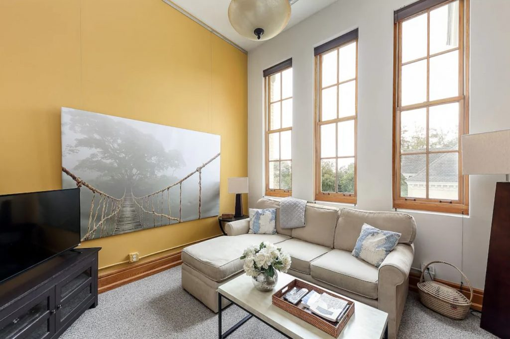 The cozy living room of a condo in Traverse City. It has three large windows with natural wood trim. The back wall is painted a buttercup yellow and the wall with the windows is cream. There is a cream sectional sofa, a tall lamp, and a tv on a stand in the corner. one of the best michigan airbnbs