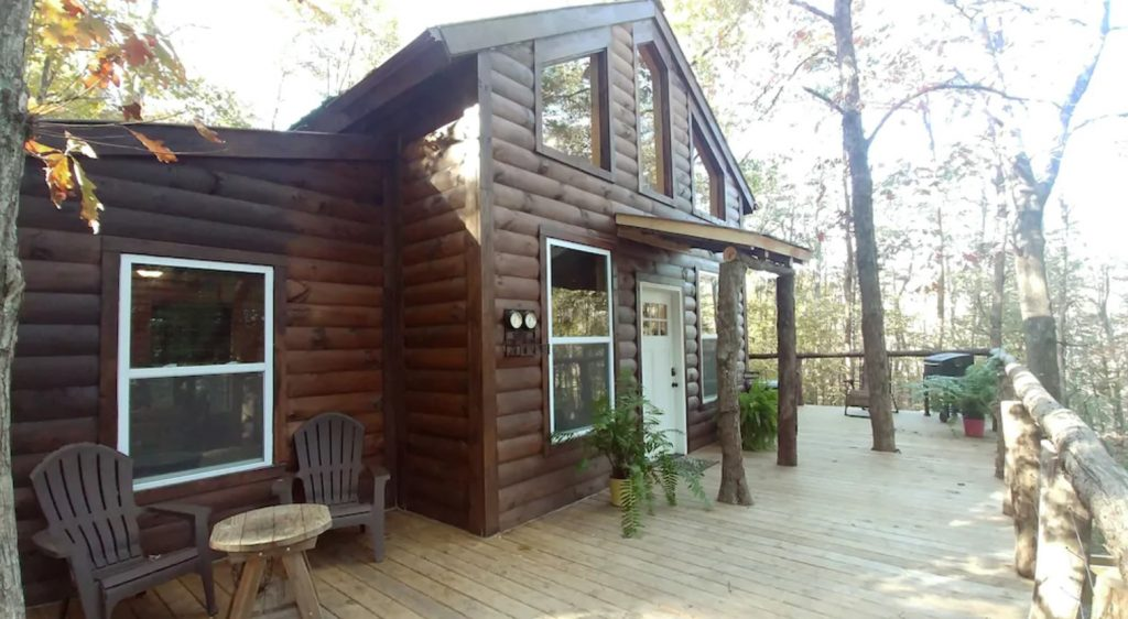 The front of a large log cabin style treehouse. It has a large front deck with seating on it, a tree growing through the deck, and a grill. The cabin has lots of windows and natural wood accents. It is surrounded by trees