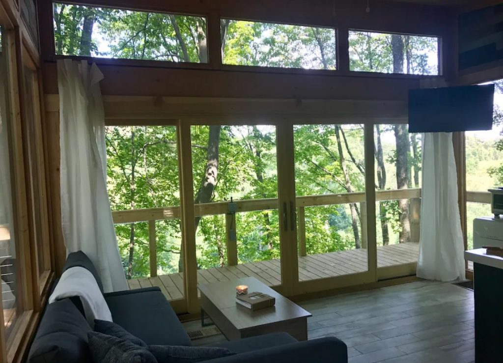 The interior of a treehouse in Ohio. It has floor to ceiling windows that look out onto the wrap around porch and the trees. Inside there is a small couch and a coffee table with a book and candle. There is a tv mounted above the windows and white curtains on the sides of windows.