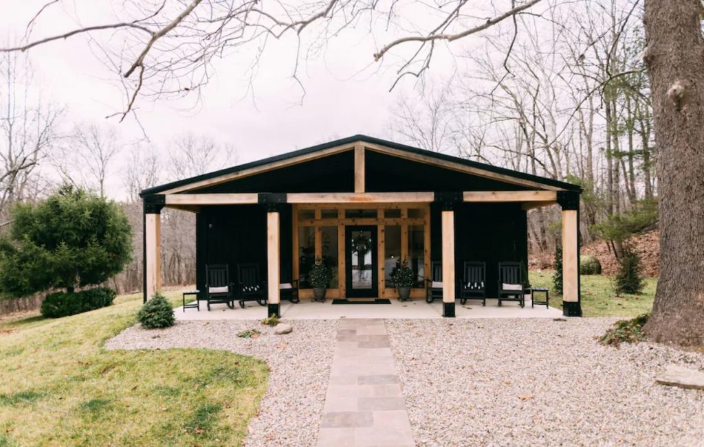 A large black cabin with a covered front porch and natural wood columns. It is on a grassy lawn and there is a pebbled area in front of the front porch. There are trees behind it with no leaves on them. One of the best cabins in Hocking Hills