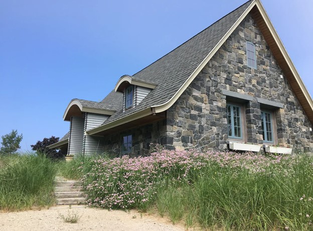 The exterior of a grey stone cottage on the shores of Lake Michigan. It is surrounded by tall grasses with pale pink and purple flowers. There are two light blue windows on the side of the cottage and a sandy path leading up to the front door.