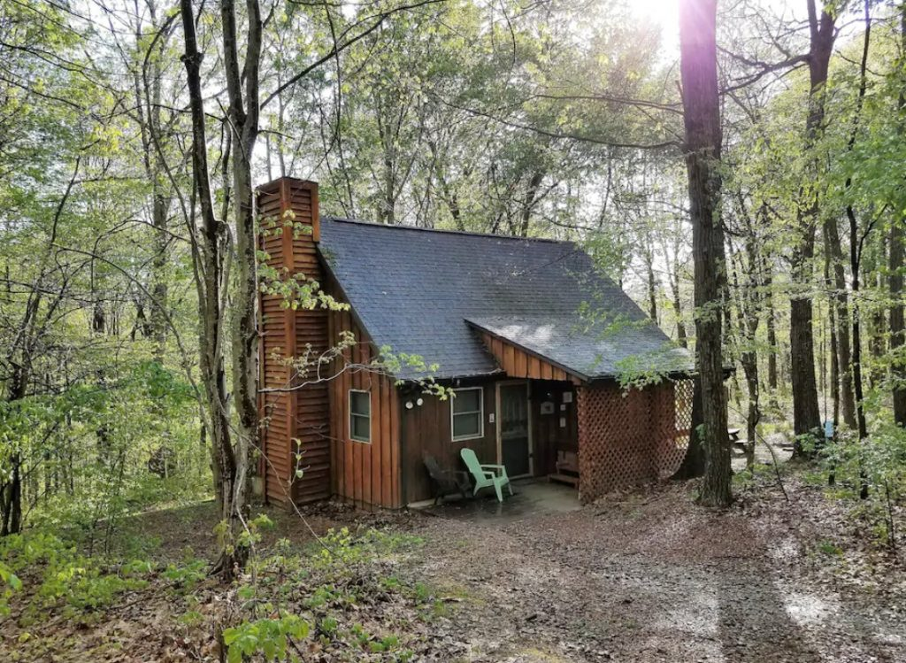 The exterior of a log cabin surrounded by woods. There are two Adirondack chairs in front of it - one is black and one is mint green. There is also a porch that is behind a privacy lattice. The wood on the cabin is kind of orange and there is a chimney.