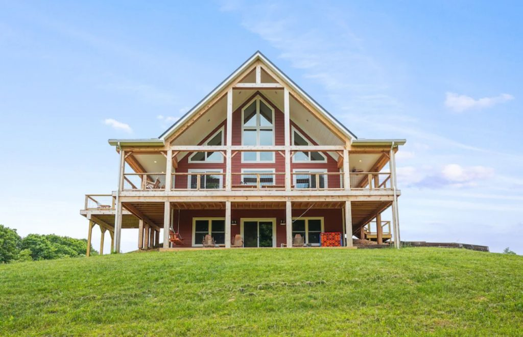 The exterior of a large red A-frame cabin. It has tons of windows, a patio, and a deck on the second story. It is perched on top of a hill covered in green grass. One of the best cabins in Hocking Hills