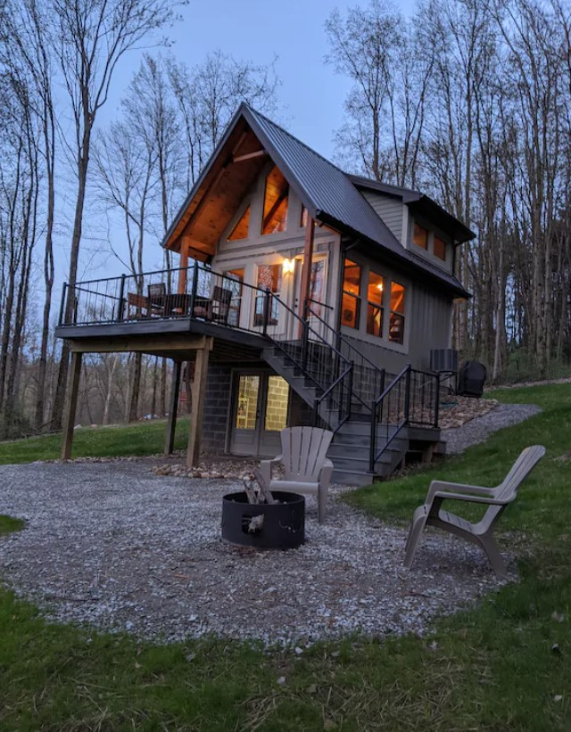 The exterior of a cabin surrounded by trees with no leaves on them. It has a second story deck, floor to ceiling windows on the front, and a set of double doors on the ground floor. There is a pebble courtyard with a firepit and chairs.