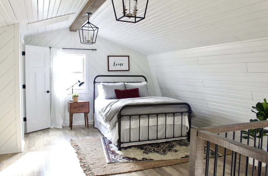 The interior of one of the cutest cabins in Ohio. It is a loft bedroom with white shiplap walls, a black iron bed with white and grey bedding, and a window with a white curtain. There are two rugs under the bed and you can see the railing of a staircase.