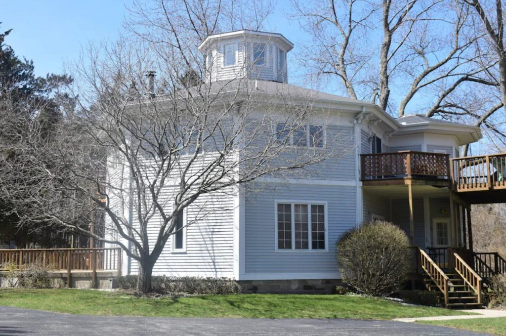 A light gray house that is shaped like an octagon. It has a peak at the top that resembles a lighthouse. There is a porch and deck on the front. It is on a green lawn and there are a few trees without leaves.