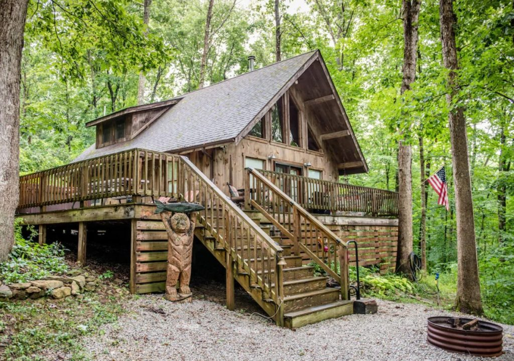 The exterior of a classic wood cabin. It has stairs leading up to the deck that wraps around the house. The house is all wood and has a classic a-frame style. Around the house you can see nothing but dense woods and there is an American flag hanging on one tree.