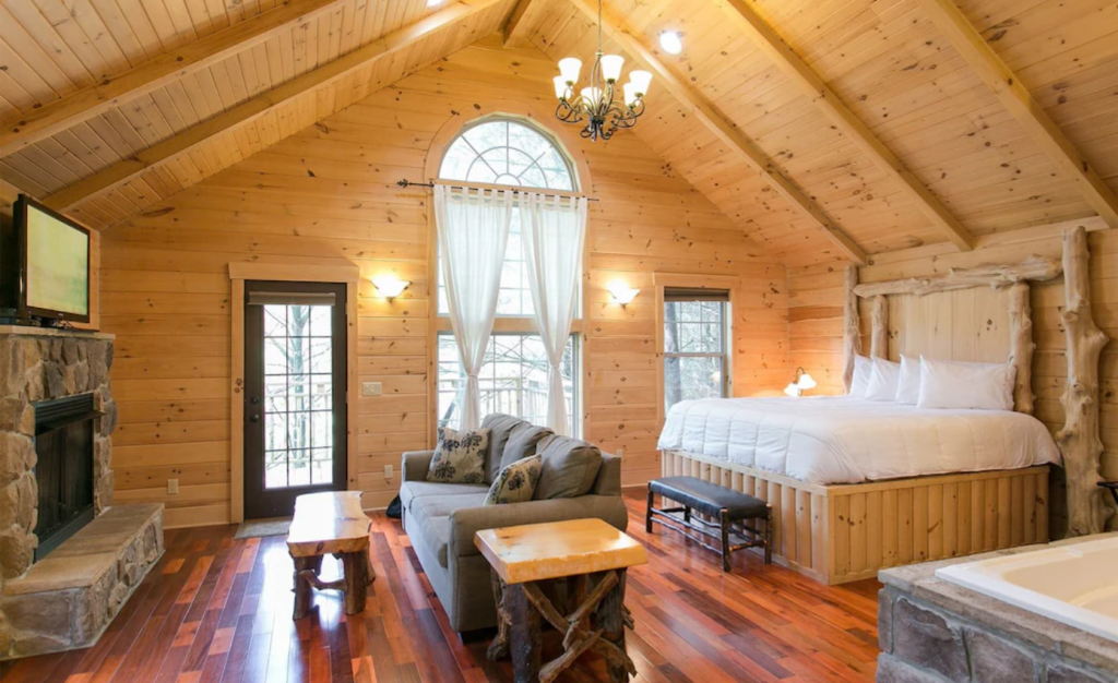 The interior of a classic log cabin decorated romantically. It is a studio style space with a large wooden bed, a couch, and a stone fireplace. You can see the corner of a hot tub. On one wall it has a door, a floor to ceiling window, and another smaller window.