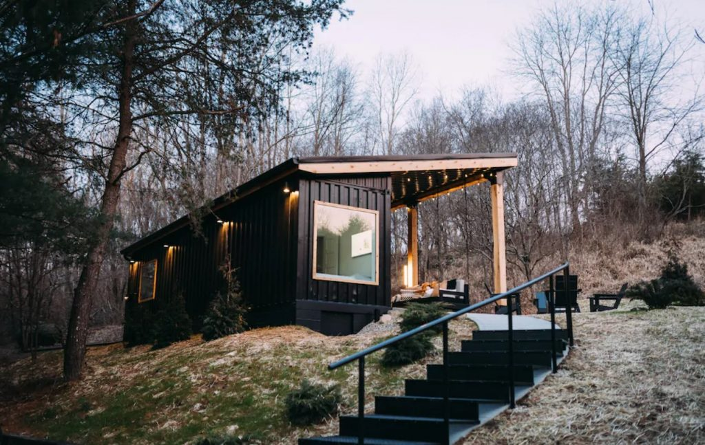 The exterior of a shipping container that has been turned into a cabin. It is painted black and there is a large window on one side. You can see the covered front porch and a porch swing. There are stairs leading up to the cabin and it is surrounded by trees with no leaves.