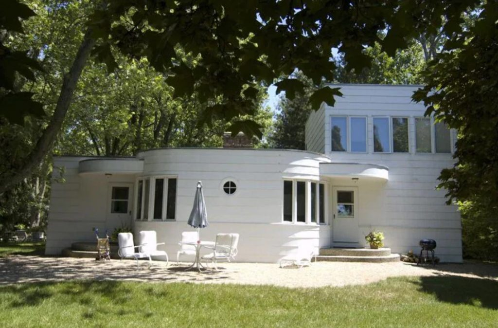The exterior of a white vintage Mod style beach house. It has a rounded section in the middle and then a taller section with windows attached to the rounded section. There is a patio in front of it with patio furniture on it.
