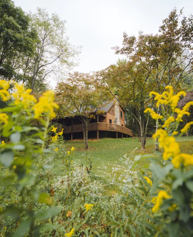 Looking through plants with yellow and white flowers towards a large cabin on a grassy area. It is a classic wood cabin with a wrap around porch and a large stone chimney. There are dense trees behind the cabin with green and orange leaves. One of the best cabins in Hocking Hills